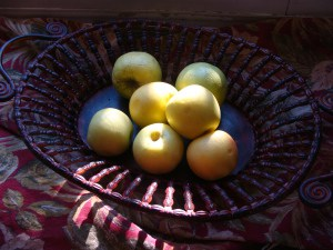 Yellow apples in a metal fruit basket on a table