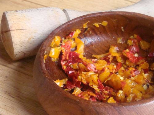 Diced roasted red and yellow peppers in a wooden bowl