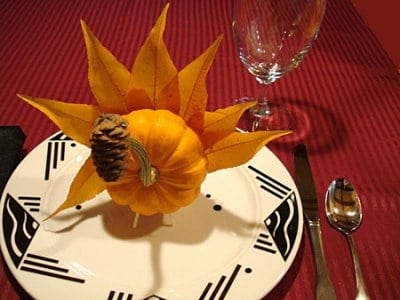 Thanksgiving place setting with a turkey made of a gourd, leaves and pine cone