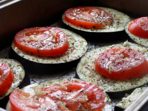 Slices of eggplant topped with slices of tomato and seasonings