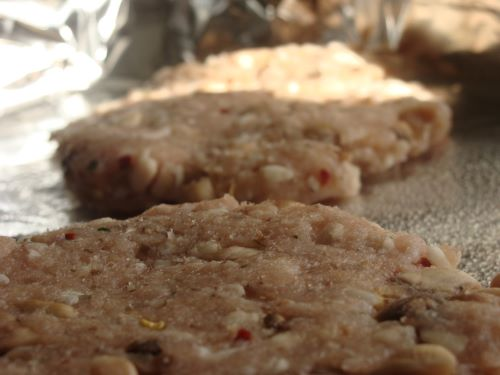 Raw turkey patties on a foil-lined pan