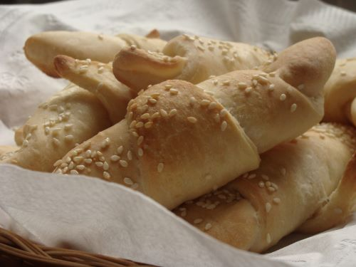 Golden vegan croissants topped with sesame seeds in a parchment-lined basket