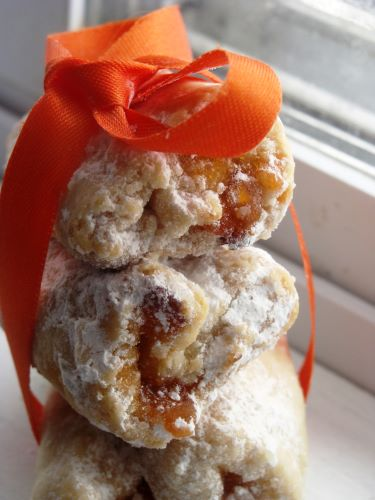 A stack of apricot cookies wrapped with orange ribbon