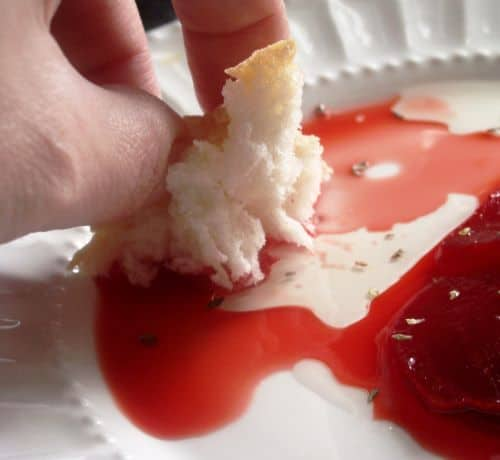 A piece of bread being dipped in red beet dressing on a white plate