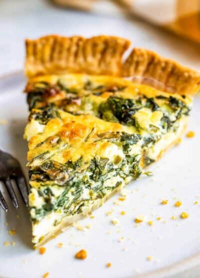 Slice of spinach quiche on a plate.