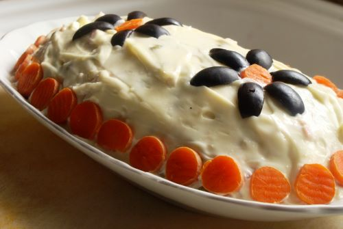 An oval platter of creamy Russian Salad decorated with sliced carrots and black olives in the shape of flowers