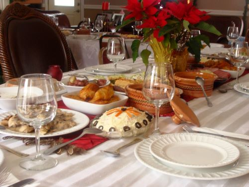 A holiday table spread with white linens, plates, wine glasses, a variety of foods and red flowers