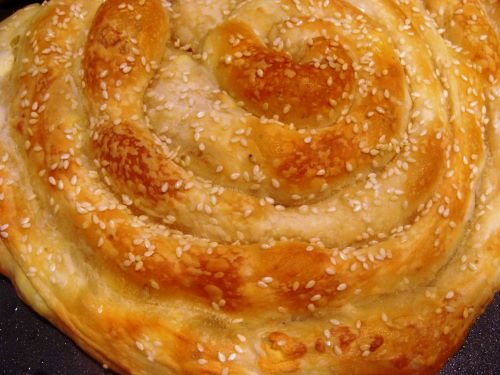 Top view of a round spiral pastry topped with sesame seeds