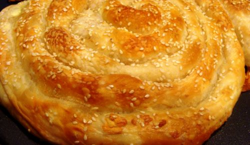 A golden spiral pastry topped with sesame seeds