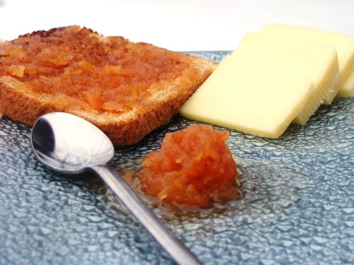 A slice of toast with quince jam and sliced cheese on a cutting board