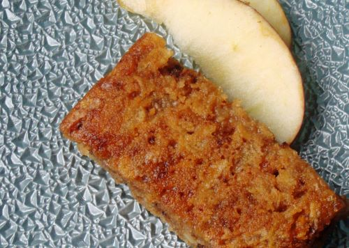 A piece of apple pie cake and two apple slices