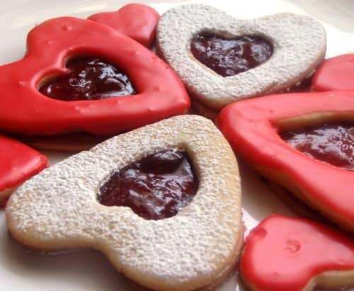 Heart-shaped Linzer cookies topped with red frosting or powdered sugar