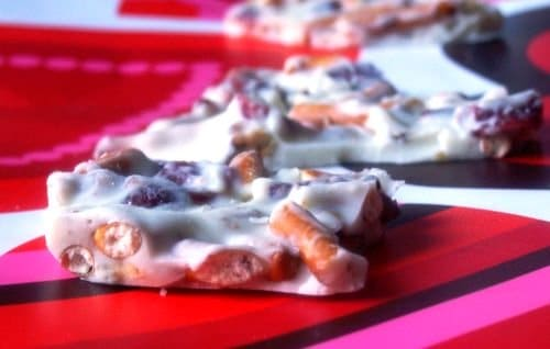 Squares of white chocolate pretzel bark on a red plate