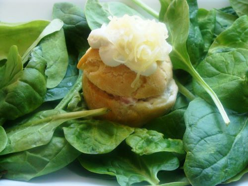 A savory cream puff on a bed of baby spinach leaves