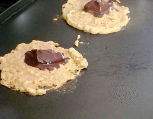 Pancake batter with a scoop of chocolate ganache cooking on a griddle
