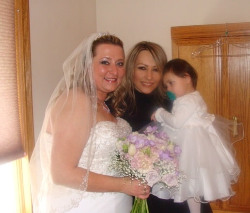 A bride with another adult female and a baby flower girl posing for a photo