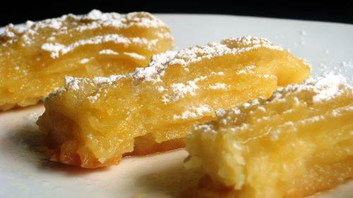 3 Tulumbi log-shaped Macedonian pastries on a plate dusted with powdered sugar