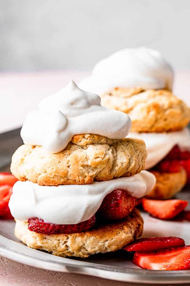 assembled strawberry shortcakes with homemade biscuits filled with whipped cream and macerated strawberries