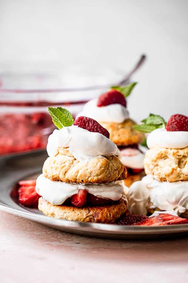 Three strawberry shortcakes desserts served on a pewter plate with a bowl of strawberries behind them
