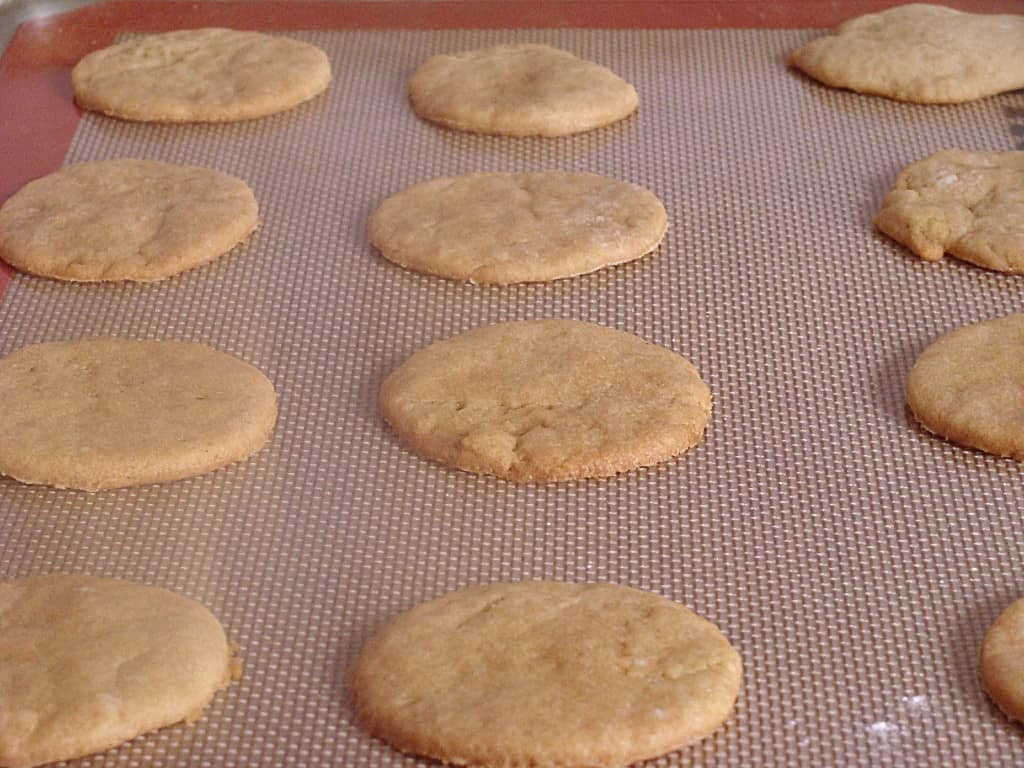 Homemade cookies being baked on a lined baking sheet