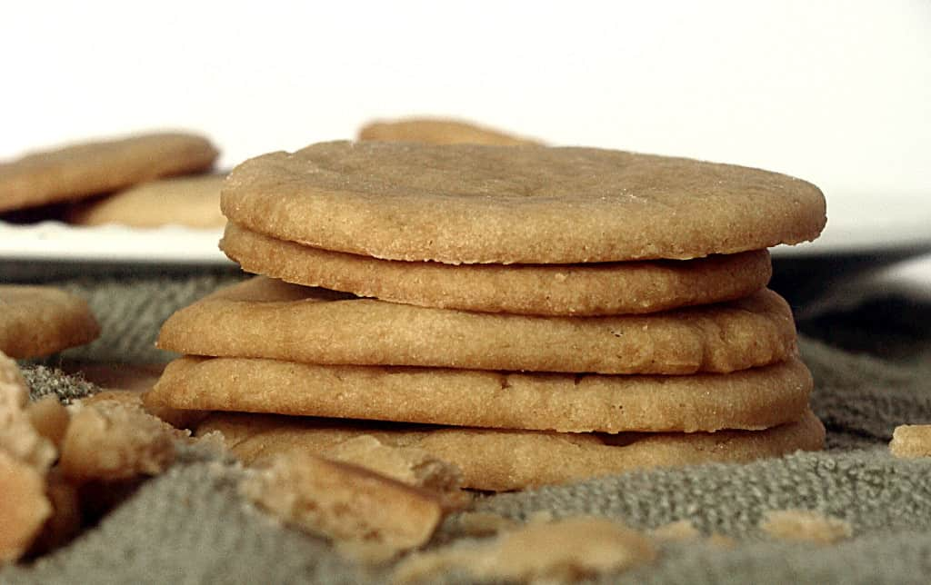 A stack of ginger cookies on a green cloth with crumbs