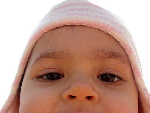 Close up image of a baby's face with a pink and white striped hat on