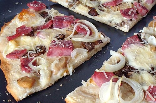 Top view of a homemade pizza with ham, mushrooms, onions, and cheese cut into four quarters