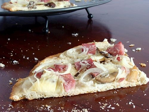 A wedge of homemade pizza with ham, onions, mushrooms and cheese