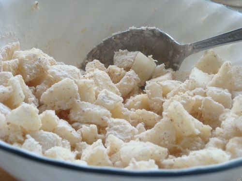 Diced pears mixed with flour and nutmeg in a mixing bowl