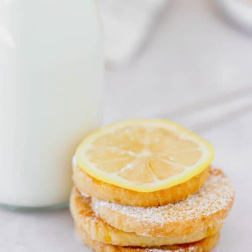 A stack of lemon cookies next to milk