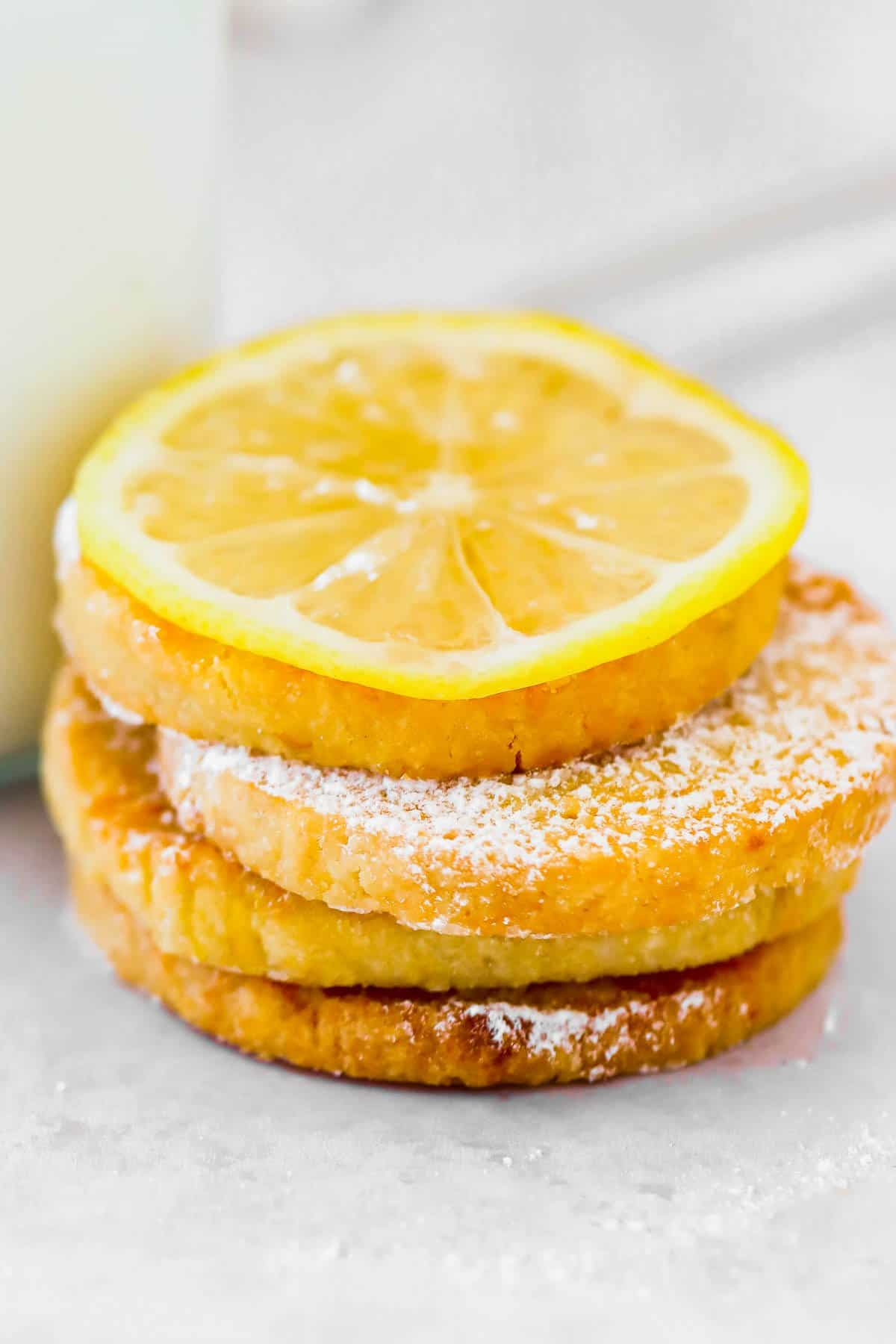 Lemon cookies stacked on top of each other in front of milk