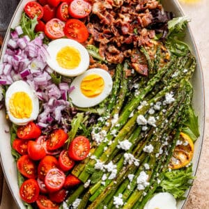 salad greens topped with chopped red onions, crumbled bacon, halved eggs, and asparagus spears