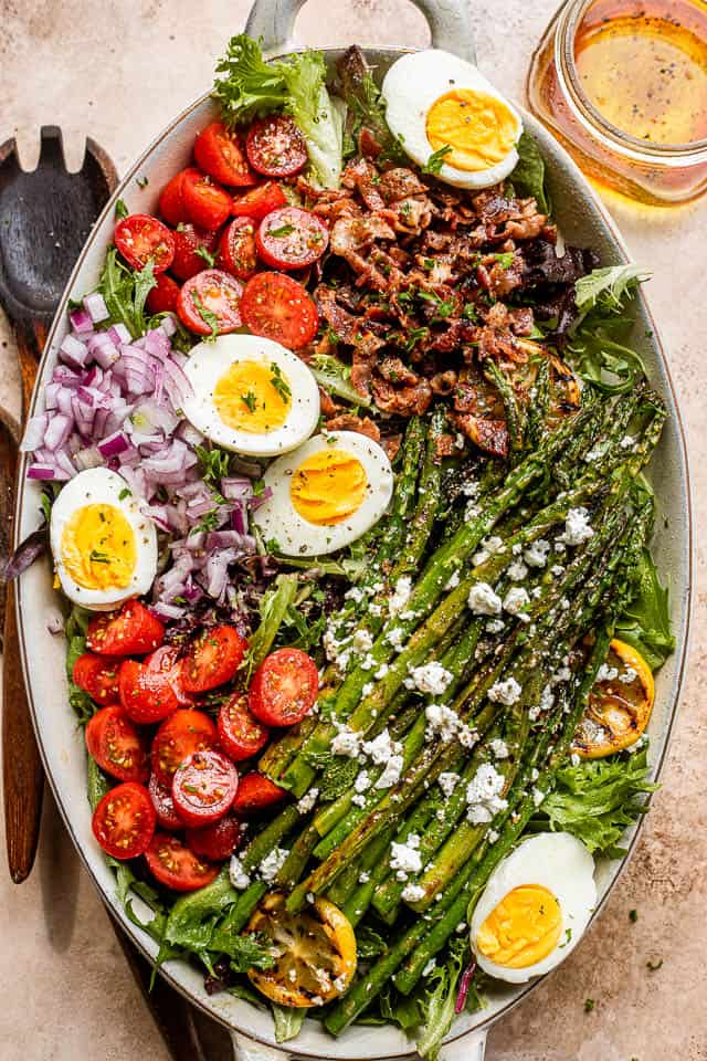 asparagus, eggs, bacon, and tomatoes on top of lettuce leaves in a long oval plate