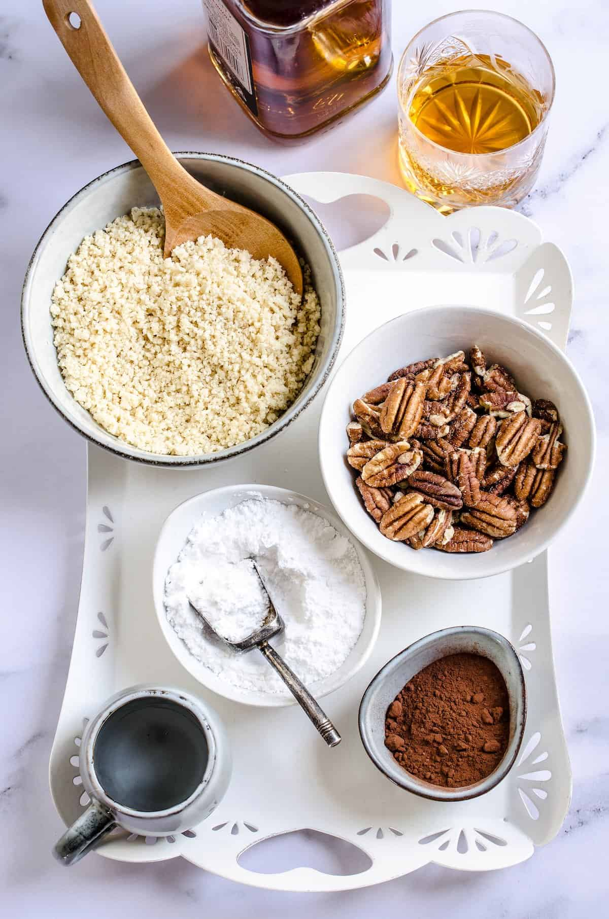 Bowls on a white tray with pecans, vanilla wafer crumbs, powdered sugar and cocoa.