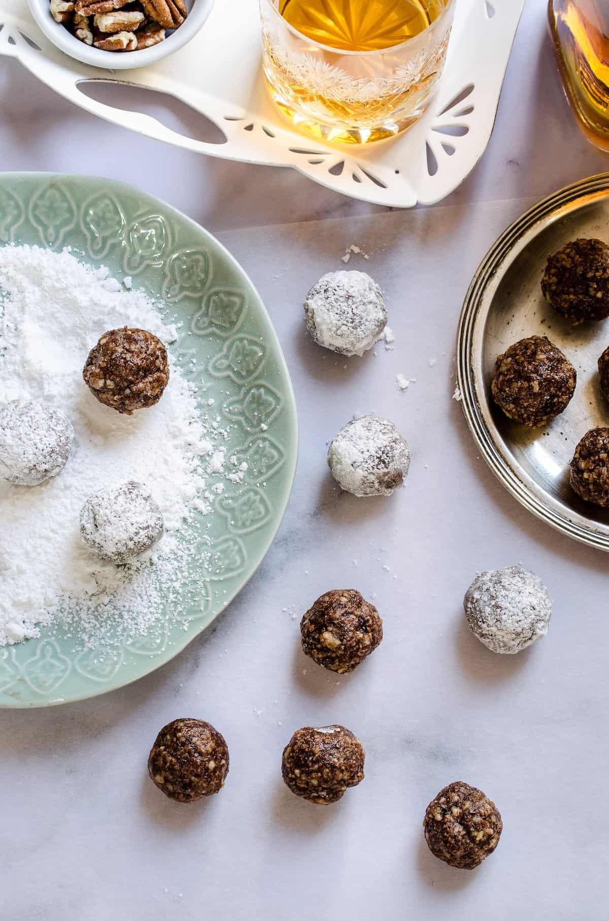 A green plate with powdered sugar next to bourbon balls and a glass of bourbon