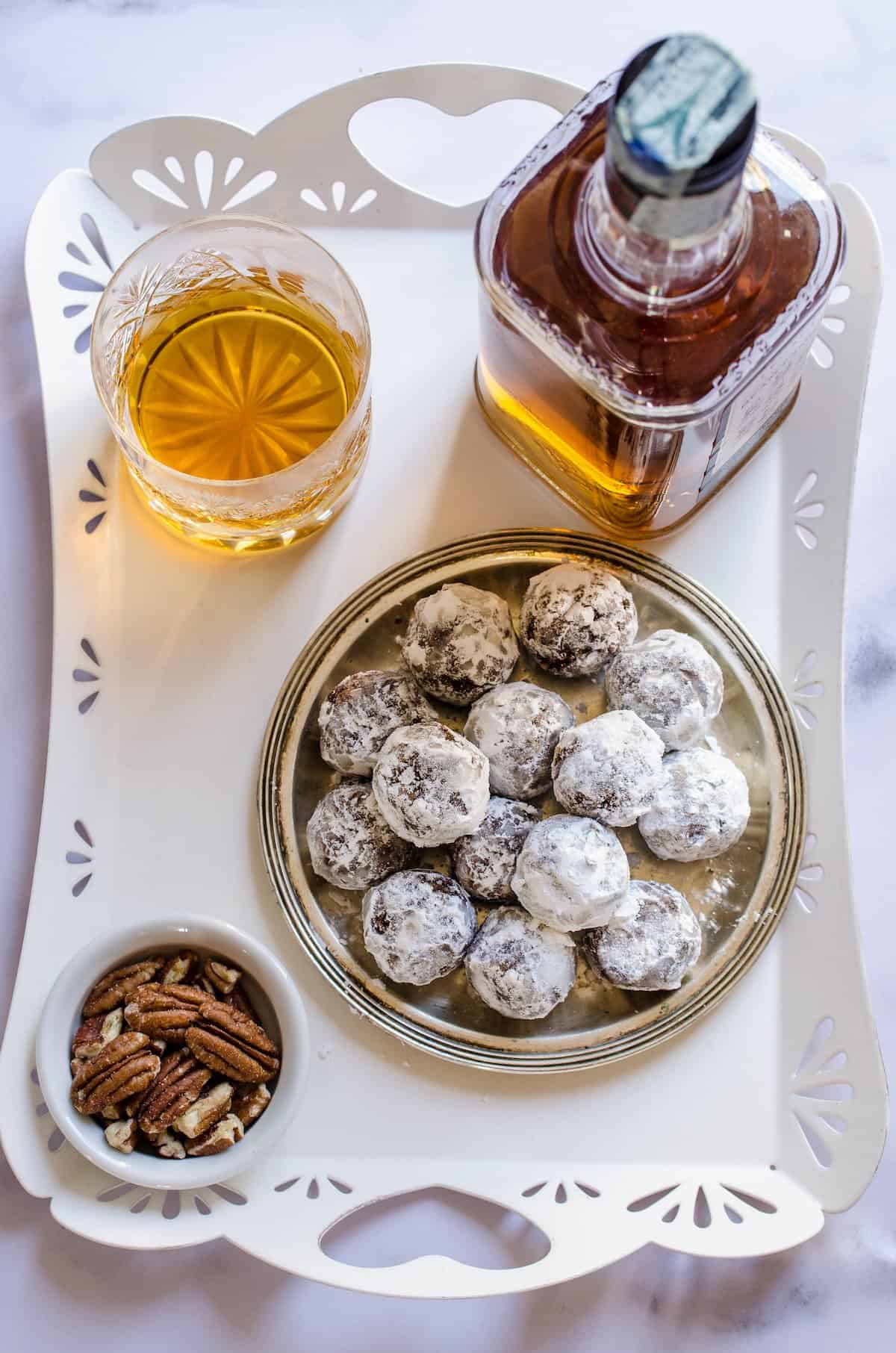A plate of bourbon balls next to a glass and bottle of bourbon