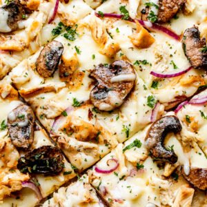 top view of a grilled pizza topped with Cheese, mushrooms, chicken, and red onions