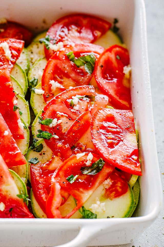 Layers of zucchini slices and tomato slices topped with garlic.