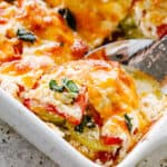 Scooping out zucchini and tomato casserole.