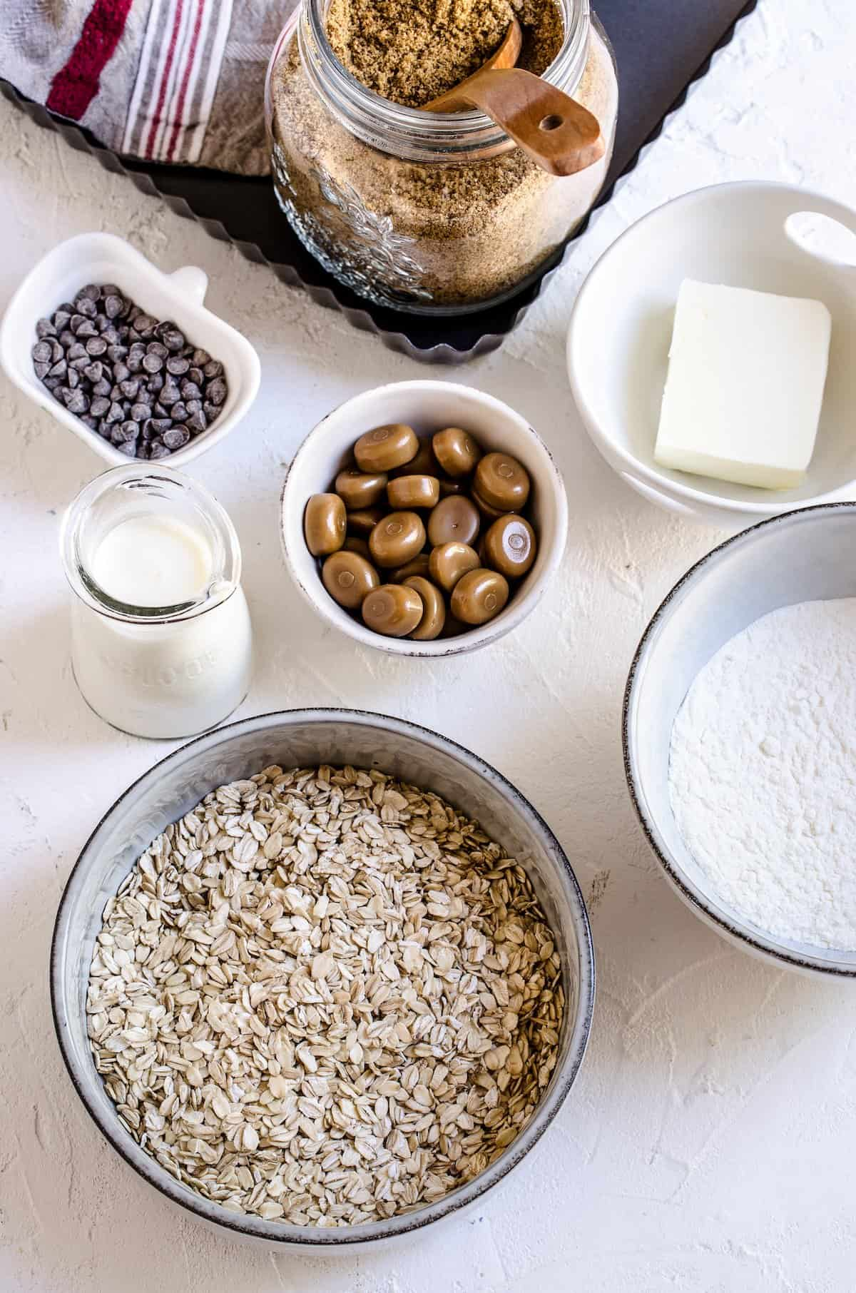 Oats, caramels, sugar and other carmelita ingredients in small bowls