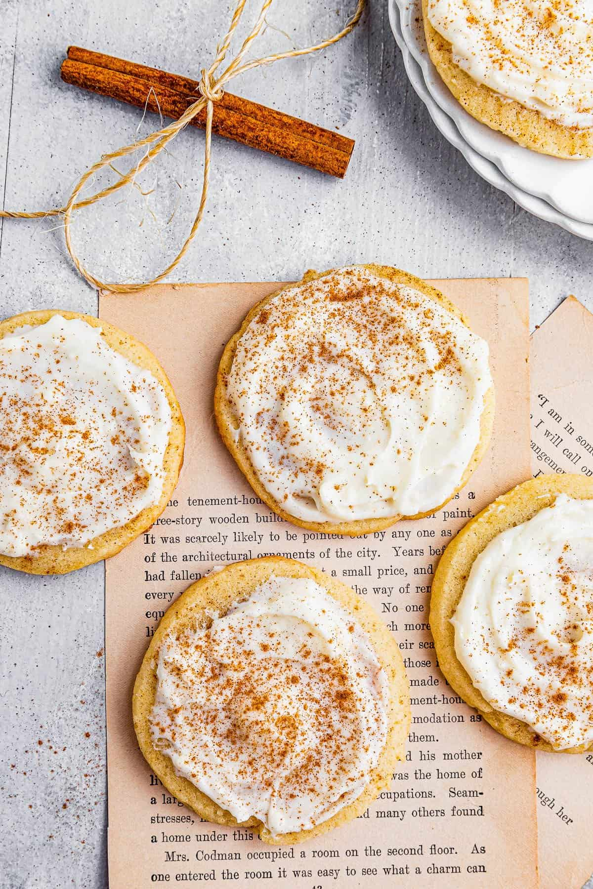 Frosted Cinnamon Swirl Cookies on Top of Two Ripped Out Book Pages Beside Two Cinnamon Sticks