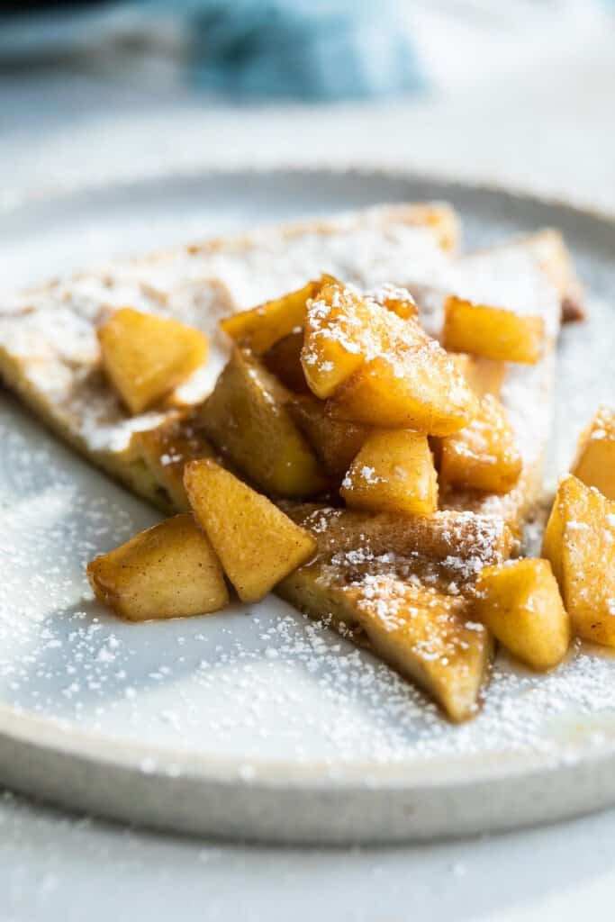 Dutch baby pancake slice with fried apples.