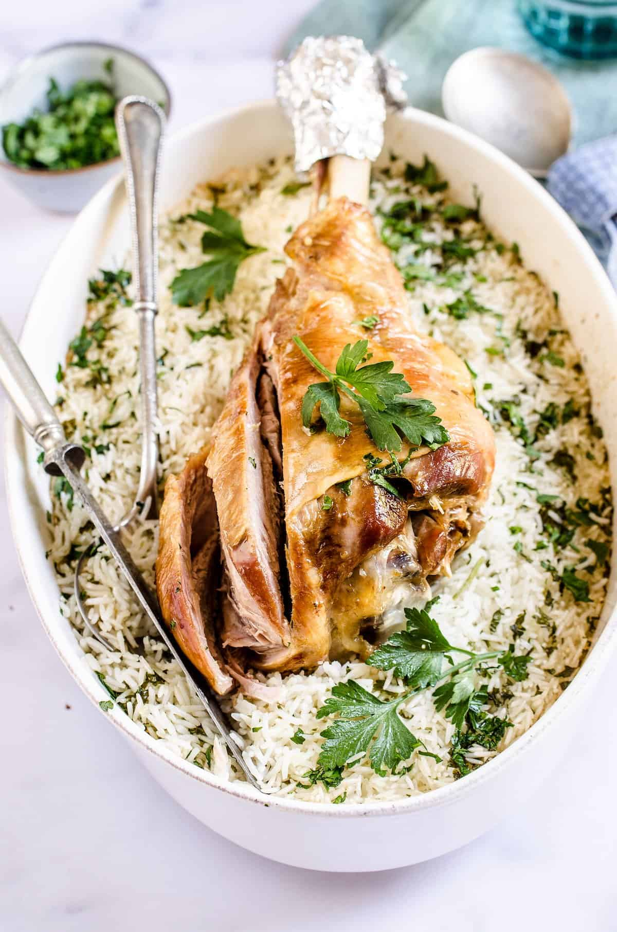 Sliced turkey over baked rice and herbs.