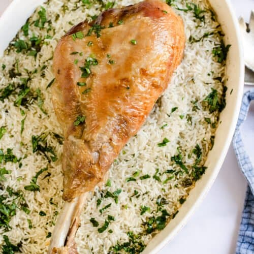 A large turkey leg over a bed of rice.