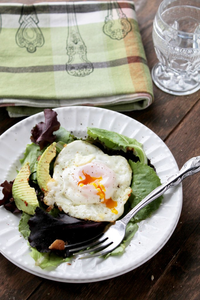 A white plate filled with salad, avocado and topped with a fried egg