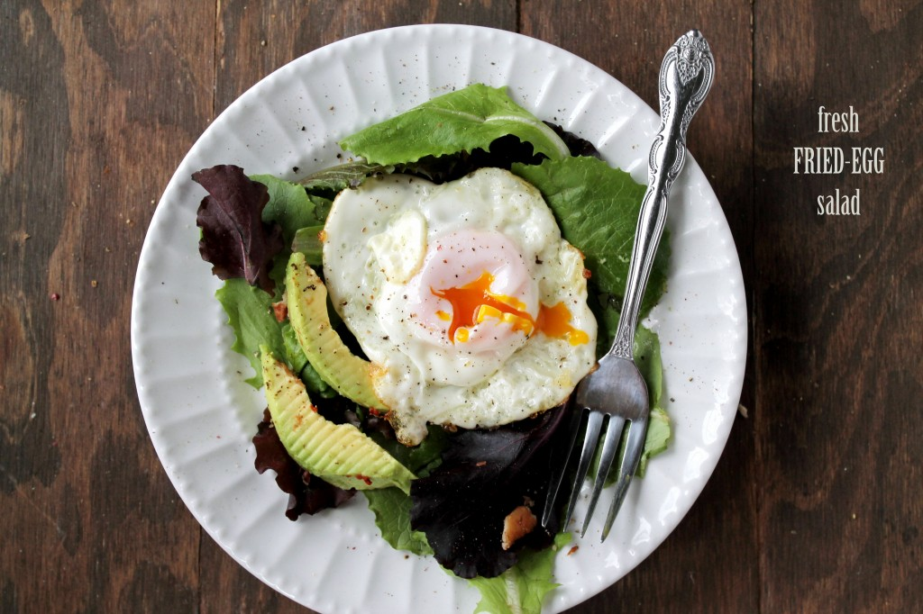 A fried egg with a broken yolk sits on top of a fresh salad with avocado on a white plate