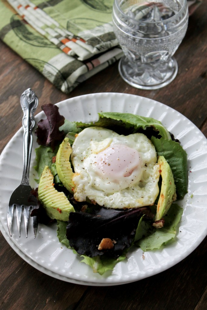 A white plate filled with lettuce, avocado and topped with a fried egg