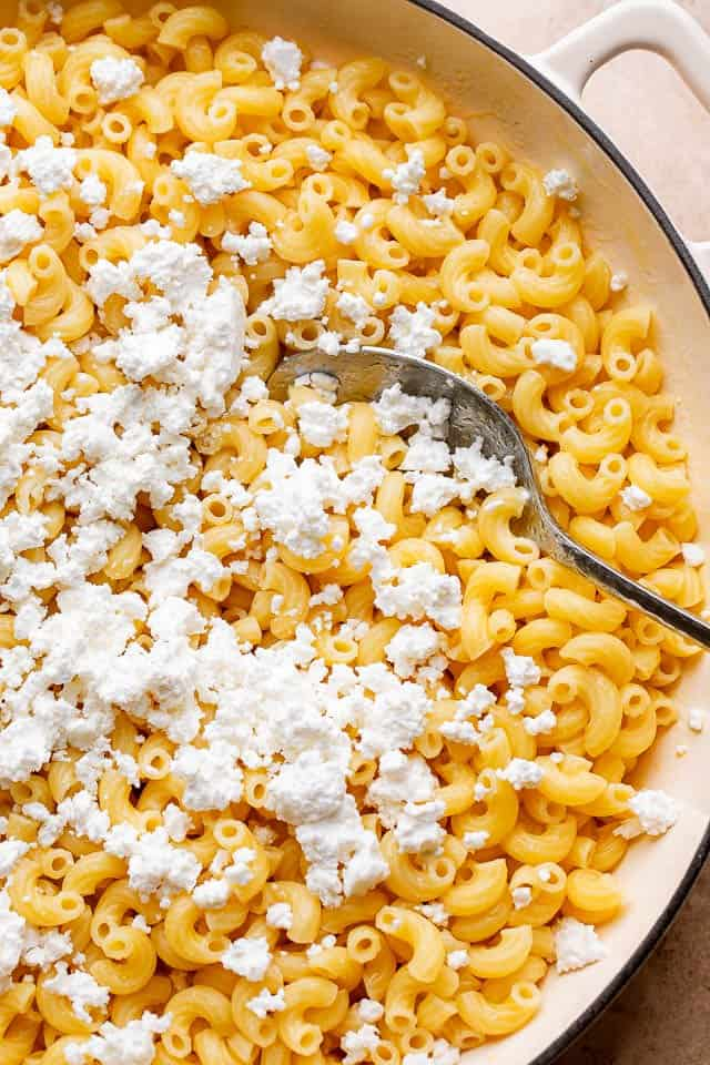 mixing feta cheese into cooked elbow macaroni