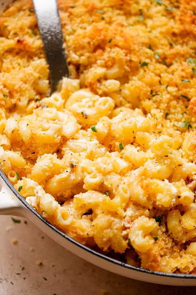 scooping out macaroni and cheese from baking dish
