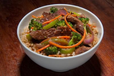 Beef stir fry with broccoli and carrots over rice in a bowl